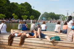 People sitting and lying near the fountain pond Stock Photography