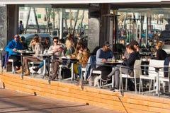 People sitting in one of the restaurants along the promenade in Portixol. Palma, Majorca. PALMA, SPAIN - DECEMBER 6, 2017: People sitting in one of the Stock Photography