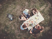 People sitting outdoor at the table celebrating party in the fields royalty free stock photography