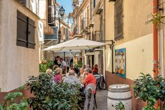 People sitting at the outside bar in a narrow street in the historic center of Monreale. stock photography