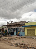 People sitting outside a shop. In Kenya, picture taken in May 2014 on a cloudy day.It´s a vertical imagen Stock Photos