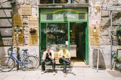People sitting outside the shop. PALERMO, ITALY - MAY 12, 2016: People sitting outside the shop only potatoes, Via Vittorio Emanuele, Palermo, Sicily Royalty Free Stock Photos