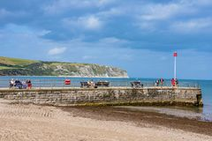 People sitting on a pier in Swanage. SWANAGE, UNITED KINGDOM - SEPTEMBER 07: This is a view of a waterfront pier with people sitting and relaxing on September 07 royalty free stock photos