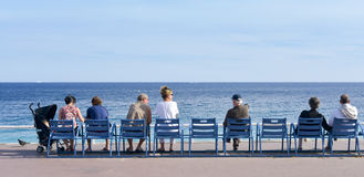 People sitting at the Promenade des Anglais in Nice, France Royalty Free Stock Image