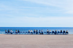 People sitting at the Promenade des Anglais in Nice, France Royalty Free Stock Photo