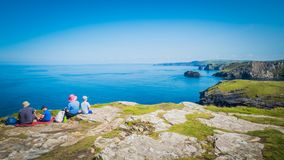 Family is sitting on a cliff at Tintagel castle in Cornwall, England with the Atlantic Ocean coastline stock photo