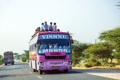 People sitting on the Roof of an Overland bus at the Jodhpur Highway in Rajasthan, India Stock Photography