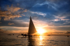 People sitting on sailboat at  ocean and looking  sunset Stock Photography