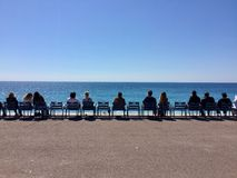 People sitting beside the sea Stock Images