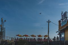 People sitting in seatings under umbrellas next to Nathan`s famous hotdogs restaurant under blue sky, in Coney Island stock photo