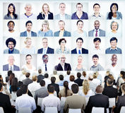People Sitting with Set of Business People's Faces Royalty Free Stock Photo
