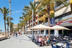 People sitting in sidewalk cafe in the seafront promenade of Torrevieja , Spain royalty free stock photos