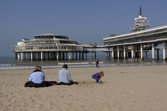 People sitting in the spring sun before the Pier of Scheveningen Stock Image