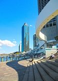 People sitting on steps near the Eagle Street Pier with sky scrapers in the background in the CBD Brisbane Queensland Australi Stock Photo