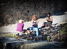 People sitting on stone wall