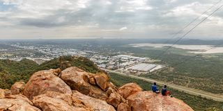 People sitting on the stones on the mountain with Gaborone city stock photos