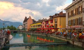 People sitting at street cafe and walking along Le Thiou river in Annecy France at late evening. Stock Image