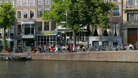 People sitting in the sun at a Canal in Amsterdam, Netherlands. People enjoying a sunny day at the Keizersgracht Canal, Amsterdam, Holland, Netherlands, Europe stock video footage
