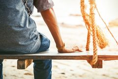 A man sitting on the swing in the beach with sun light. stock image
