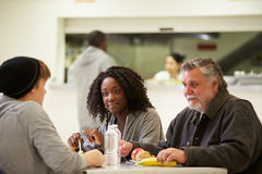 People Sitting At Table Eating Food In Homeless Shelter. Chatting To Each Other Royalty Free Stock Photography
