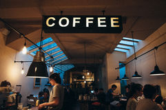 People Sitting at Table Under Coffee Signage Stock Photos