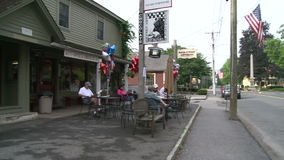 People sitting at tables along the road at a sidewalk cafe stock video