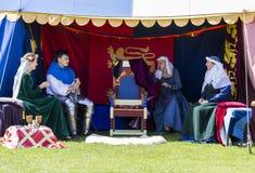 People sitting in tent. Medieval Display. Warkworth, Northumberland. England. UK. Stock Photos