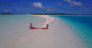 2 people sitting together a romantic young couple on a tropical island of white sand beach and blue sky and. Two 2 people sitting together a romantic young stock video