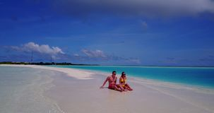 2 people sitting together a romantic young couple on a tropical island of white sand beach and blue sky and. Two 2 people sitting together a romantic young stock footage