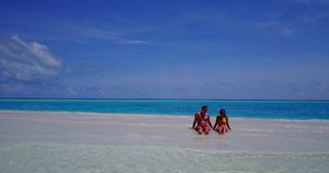 2 people sitting together a romantic young couple on a tropical island of white sand beach and blue sky and. Two 2 people sitting together a romantic young stock video footage