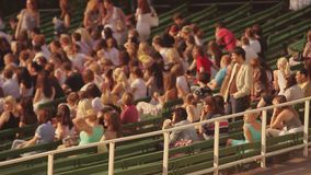 People sitting on tribune at summer event. Stadium. Crowd. Adults, youth. Sunny evening. People sitting on tribune at summer event. Stadium. Crowd. Adults youth stock footage