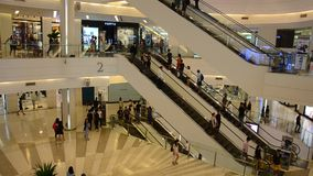 People sitting and wait at meeting point and people walking and use escalator stock video footage