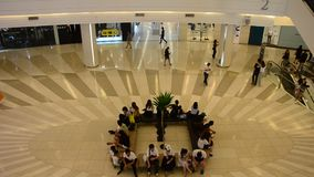 People sitting and wait at meeting point and people walking and use escalator stock footage