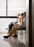 People Sitting In Waiting Area Royalty Free Stock Photography