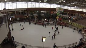 People skate on large indoor ice ring. Royalty Free Stock Photography