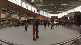 People skate on large indoor ice ring. Time Laps Royalty Free Stock Images