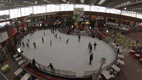 People skate on large indoor ice ring. Time Laps Stock Photography