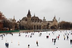 People skating on ice on an ice skating rick with a castle in the background royalty free stock photography