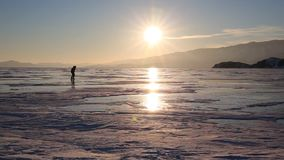 People skating on the ice of lake Baikal at sunset stock footage