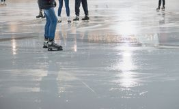 People skating in park on winter skating ice rink Stock Photo