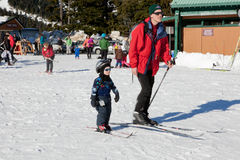 People in the Ski Field. A father with his toddle son are skiing in the field Royalty Free Stock Photo