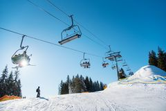 People on ski lift in the mountains. Silhouette of skier on snowy slope and low angle shot of a ski lift at ski resort in the mountains on a sunny winter day Stock Images