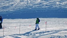 People Ski And Snowboard Past On The Snow. Skiers and snowboarders pass on sunny slope stock video