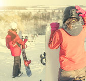 People in ski suit holding snowboards on a snowhill Stock Photo