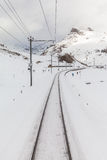 People skiing along the tracks of Bernina Express Royalty Free Stock Photo