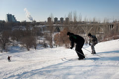 People are skiing down the hill in the city Royalty Free Stock Photography