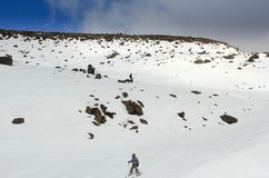 People skiing downhill from the snow mountain top following the ski route stock photos
