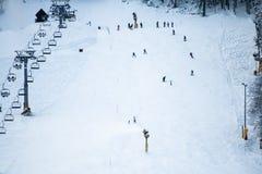 People skiing on slopes in winter scenery in Kranjska Gora in Julian Alps, Slovenia. People skiing having fun on slopes in winter scenery in Kranjska Gora in stock photo
