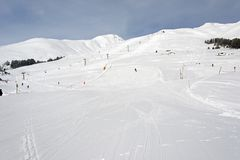 People skiing in the snow ski piste in the alps switzerland for winter holidays.  Stock Photo