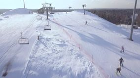 People skiing on snow slope on winter vacation at ski resort aerial view. Ski elevator fro skiing and snowboarding. People skiing on snow slope on winter stock footage